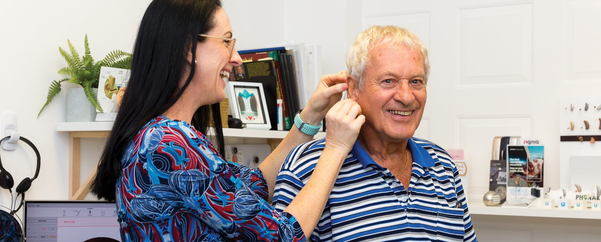 Best Audiologist in Cleveland inserting hearing aid for pensioner