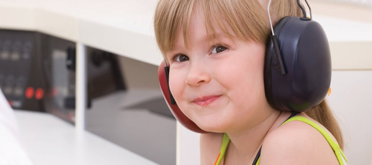 young girl wearing headphones during hearing test for kids Cleveland