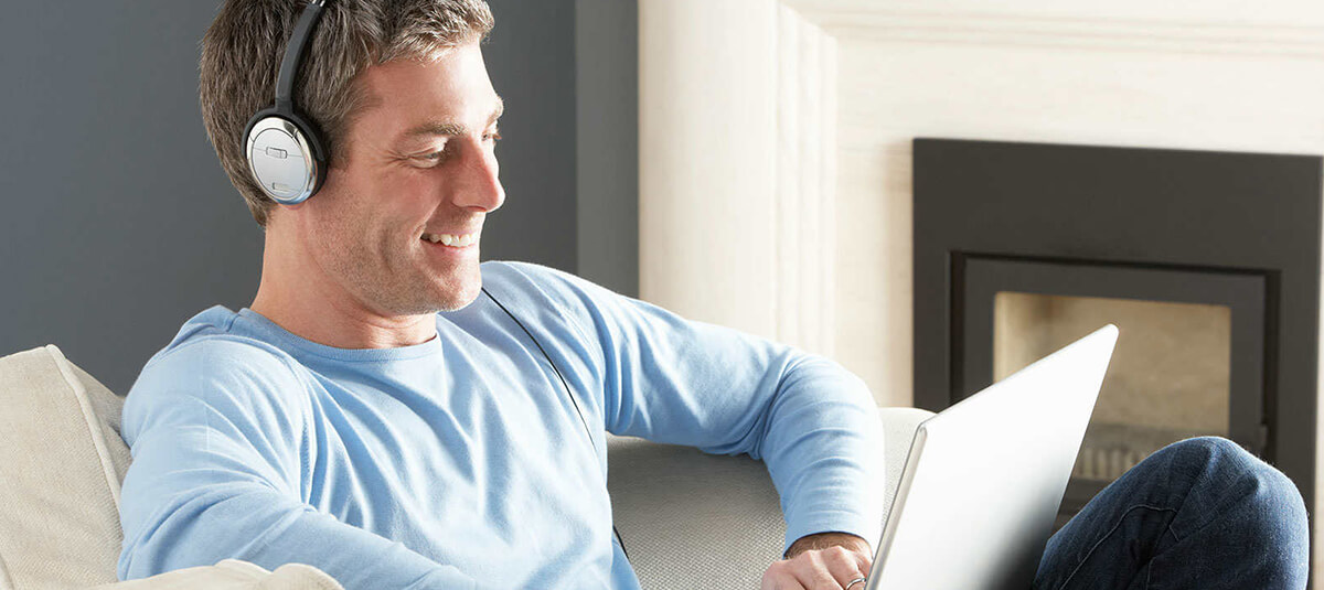 young man wearing headphones and using laptop to take an online hearing test on the A Better Ear website