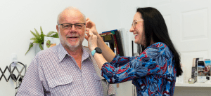 Audiologist with customer fitting hearing aid   A Better Ear